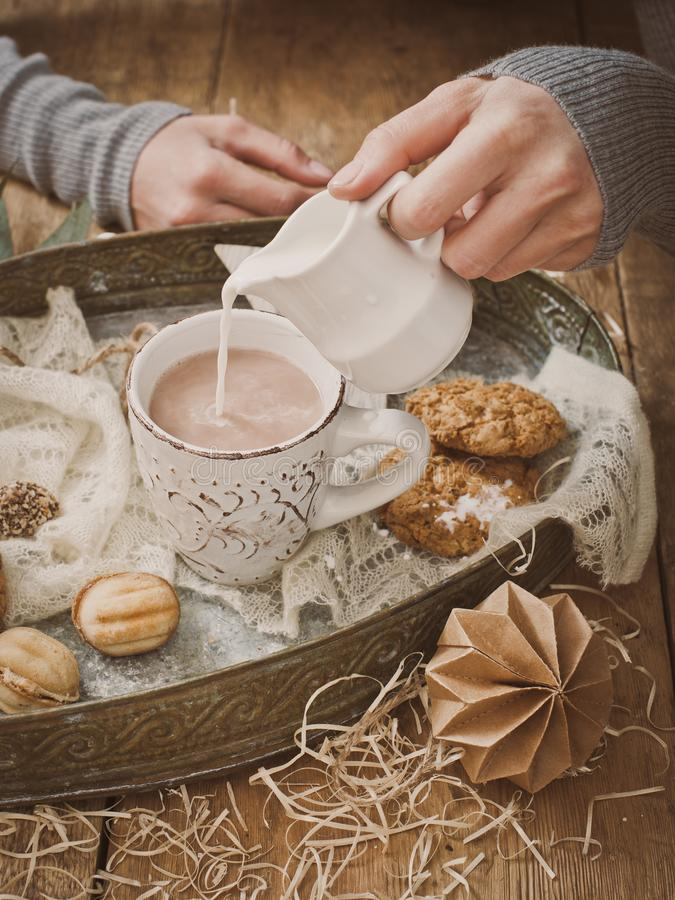Coupnum up of hand pouring milk into cocoa stock photos