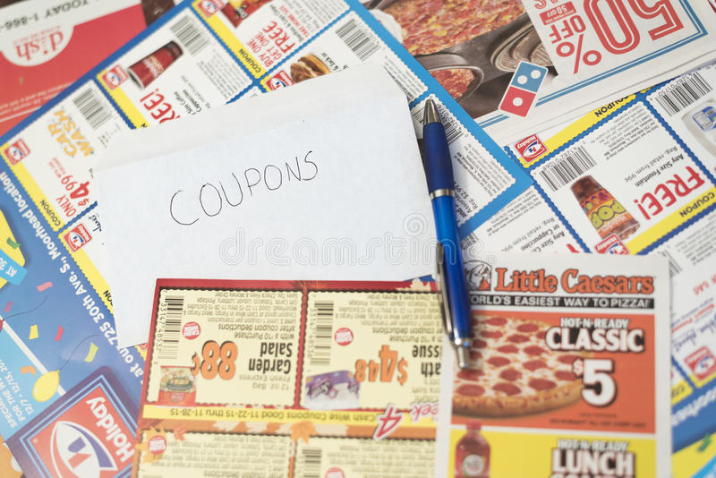 Coupons from stores and restaurants filling frame. Moorhead, Minnesota, United States - December 6, 2015: Pile of coupons from various stores and restaurants royalty free stock photo