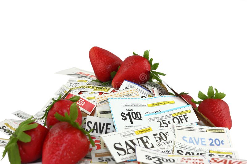 Coupons With Sweet Strawberries. Red strawberries mixed into a pile of coupons. Sweet savings concept stock photography