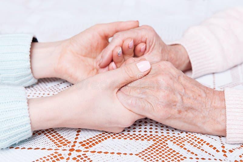 Coups de main, concept de soin aux personnes âgées Le soin est à la maison des personnes âgées photographie stock