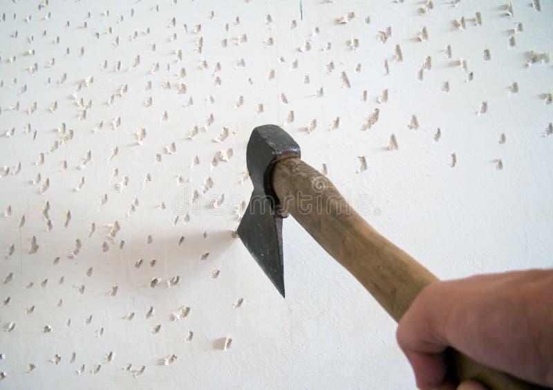 Coupure avec la hache sur le mur avant d'étendre la tuile photo libre de droits