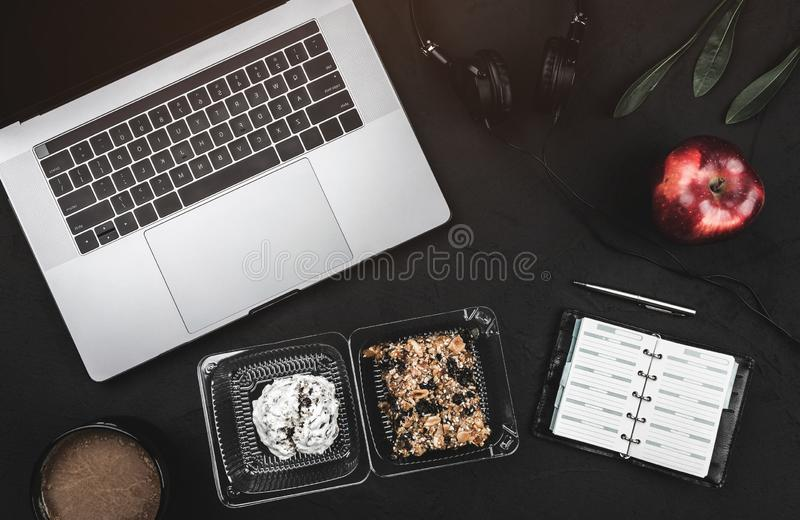 Coupure d'affaires avec les biscuits doux et la pomme fraîche Ordinateur portable, écouteurs et carnet photo libre de droits