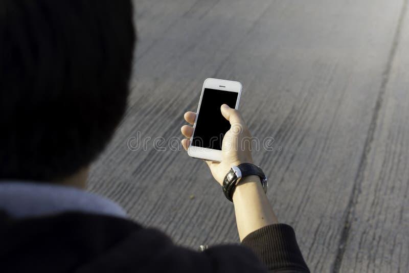 Coupure de noir de téléphone de participation de main à l'intérieur photographie stock libre de droits