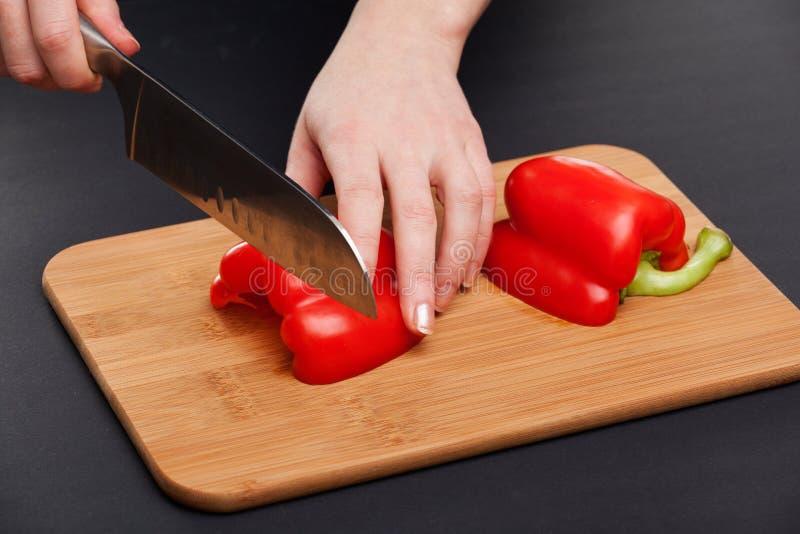 Coupure des légumes avec un couteau de cuisine sur le conseil photographie stock libre de droits
