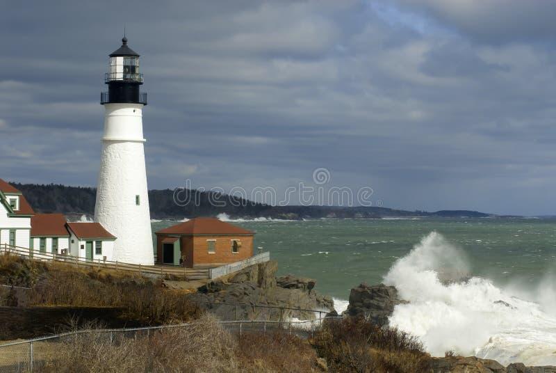 Coupures de lumière du soleil par le phare d'oin de nuages avec la rupture énorme de vagues image stock