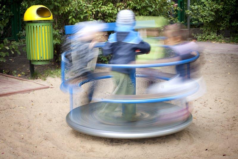 Cour de jeu avec les gosses et le carrousel photos libres de droits