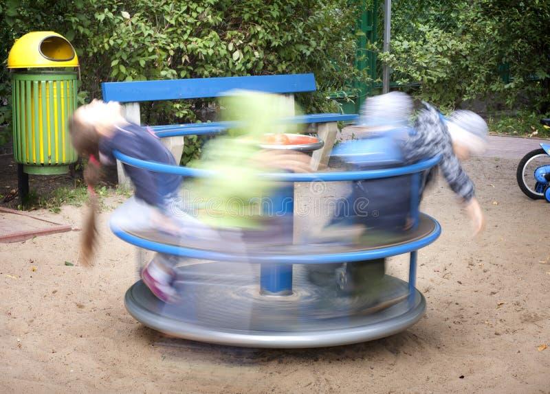 Cour de jeu avec les gosses et le carrousel photos stock