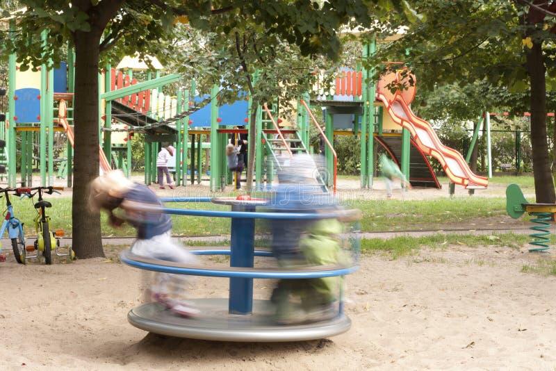 Cour de jeu avec les gosses et le carrousel image libre de droits