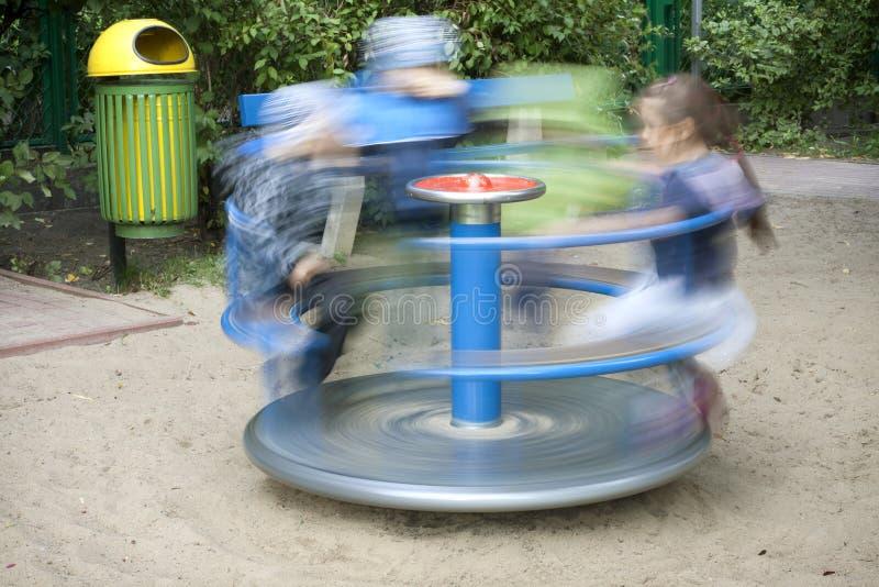 Cour de jeu avec les gosses et le carrousel photographie stock libre de droits