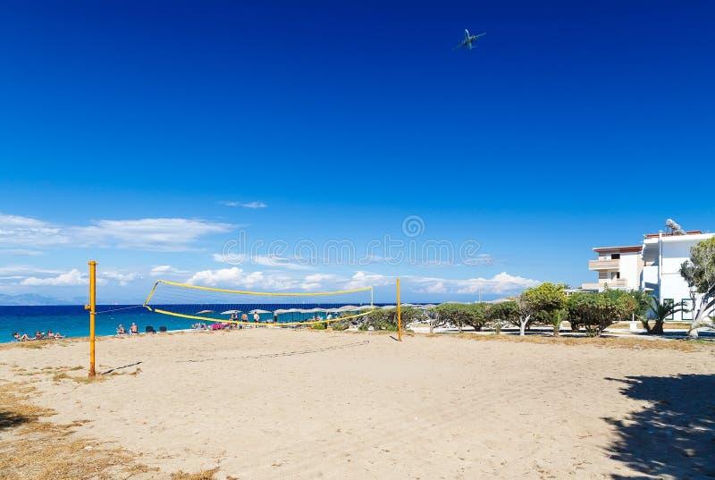 Cour de volleyball de plage le beau jour d'été en la Grèce et le ciel nuageux bleu avec l'avion photo stock