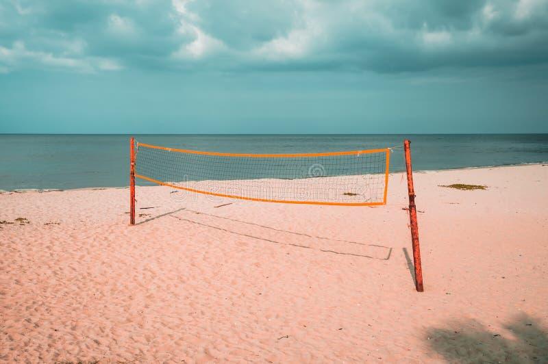Cour de volleyball sur une plage vide avec le ciel nuageux bleu image stock