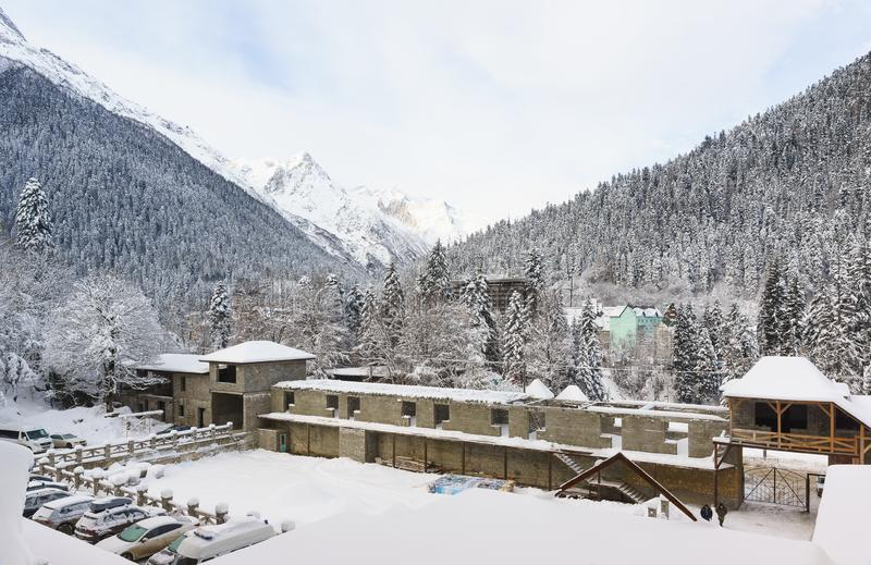 Cour du complexe d'hôtel de Dombay en hiver Le long de la barrière est la construction des centres commerciaux jour nuageux photos stock