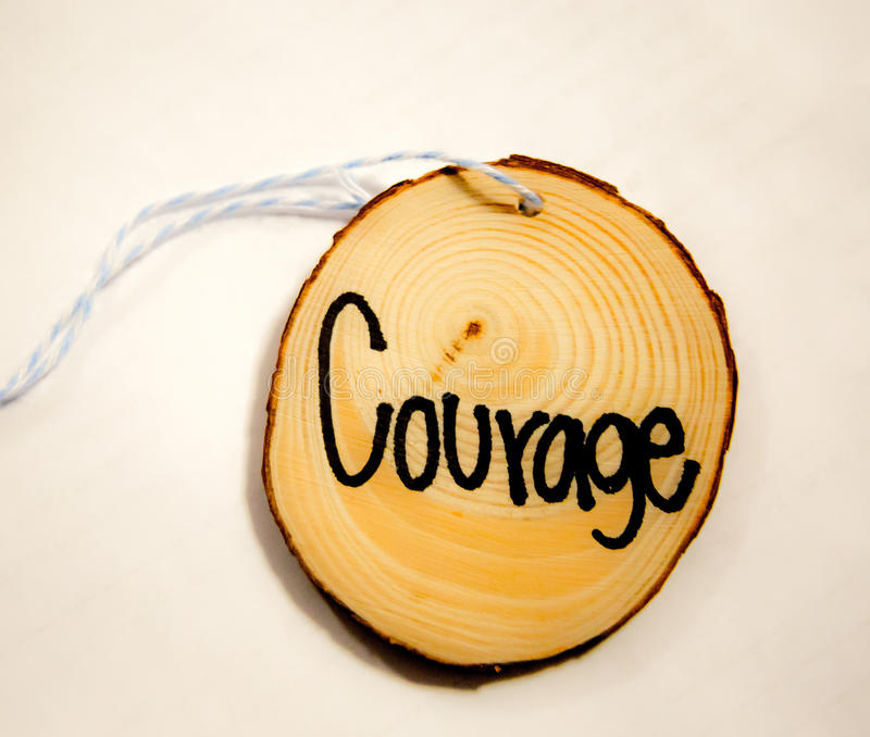 Courage. Round piece of wood on a string with the word `Courage` written on it stock photography