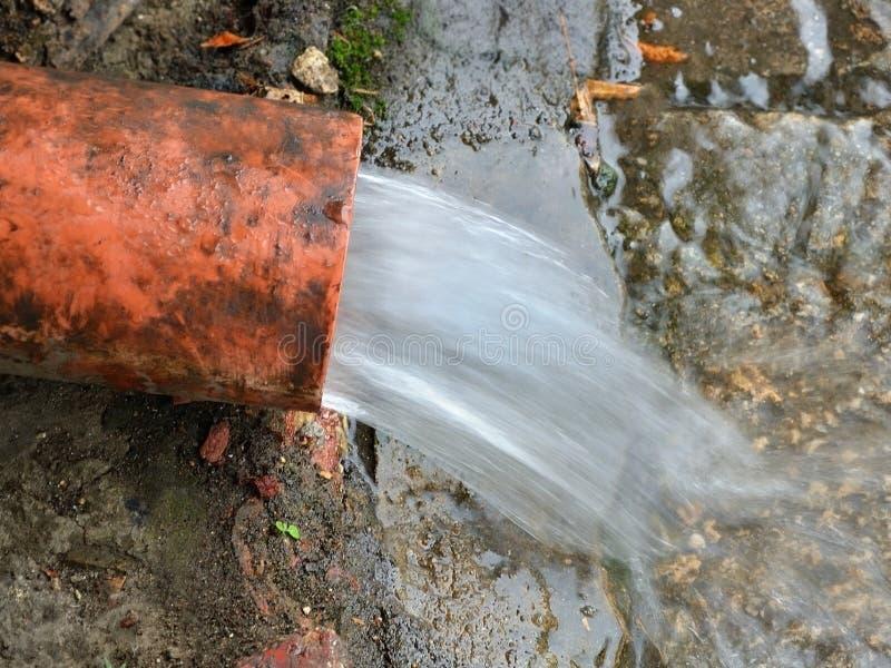 Courant des écoulements d'eau du drain de toit sur le trottoir photos libres de droits