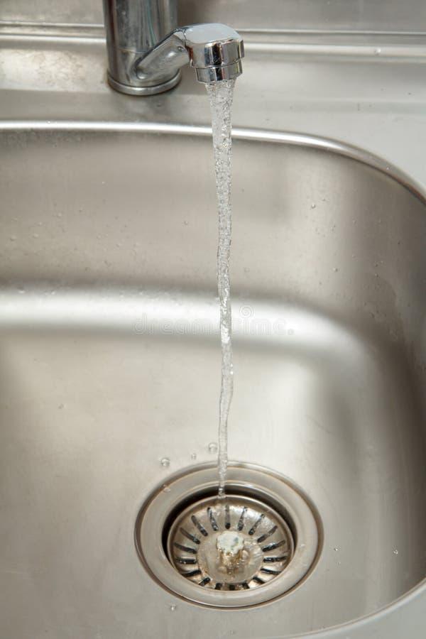 Courant des écoulements d'eau d'un robinet ouvert de chrome photo libre de droits