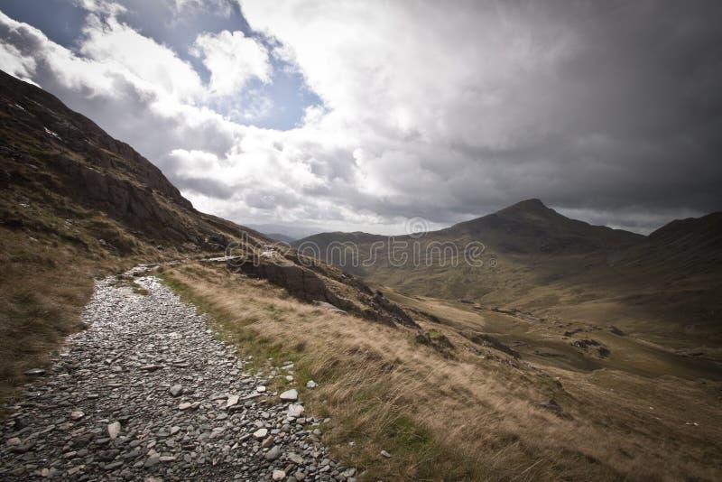 Courant et chemin de marche courbant autour du côté d'une montagne écossaise images libres de droits