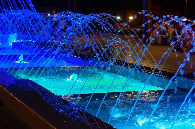 Courants bleus de la fontaine rougeoyante, fontaine lumineuse la nuit photo libre de droits