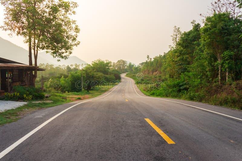 Courbe Asphalt Road Through Green Forest sur les montagnes photographie stock libre de droits
