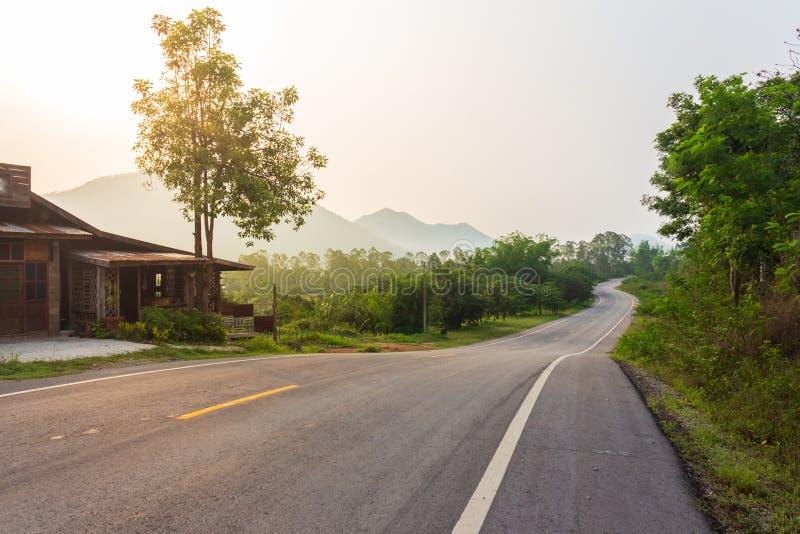 Courbe Asphalt Road Through Green Forest sur les montagnes photos libres de droits