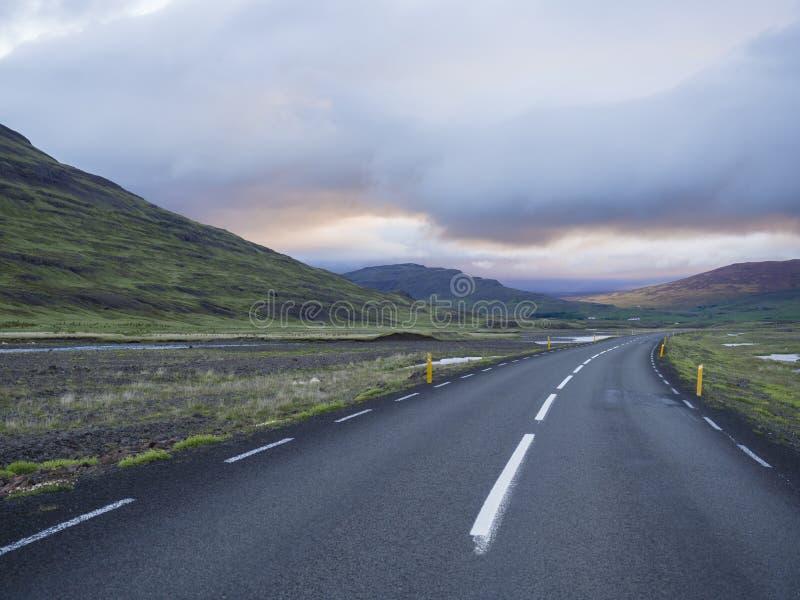 Courbe de route goudronnée par le paysage du nord vide avec les collines colorées d'herbe verte, les magmas de l'eau et le ciel d image libre de droits