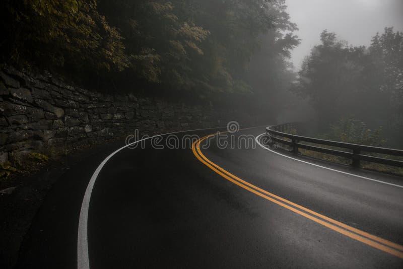 Courbe humide de route goudronnée de montagne au jour pluvieux de brouillard images libres de droits