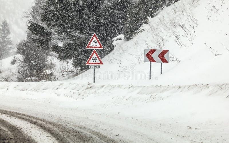 Courbe nette sur la route, avec des panneaux de route un skis prudent, la neige pendant la tempête de neige abondante blizzard en images libres de droits