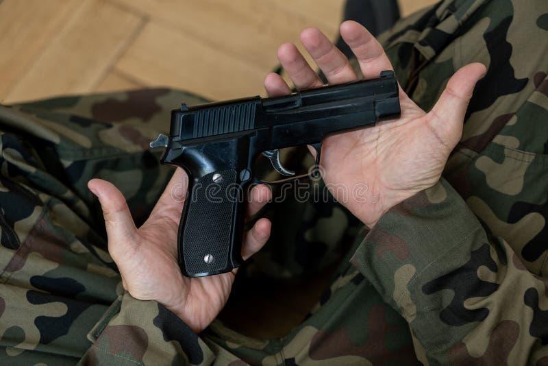 Courbe sur le soldat dans l'uniforme vert de moro avec le revolver en mains photographie stock libre de droits