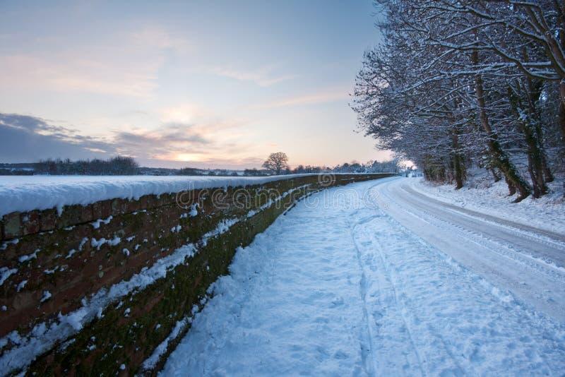 Courber la route neigeuse au coucher du soleil photo stock