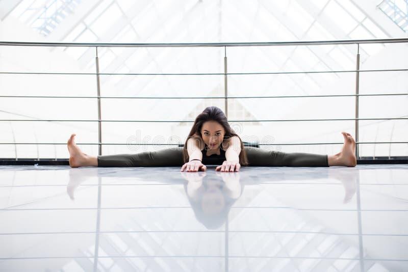 Courbure en avant posée grande-angulaire Exercice modèle de jeune forme physique attrayante dans le hall de gymnase photographie stock