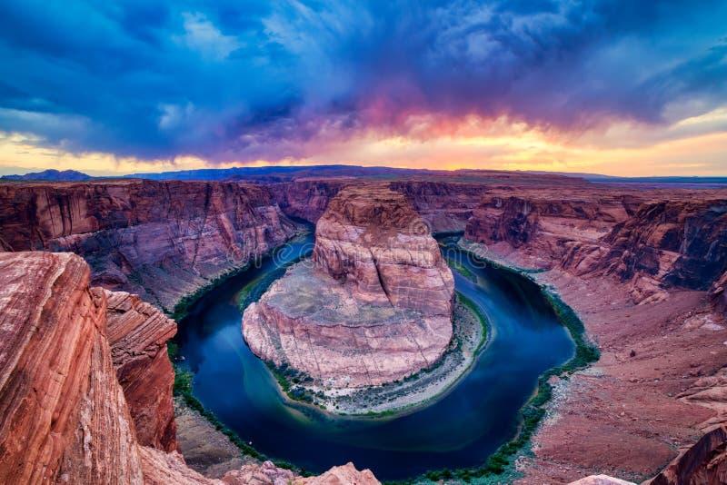 Courbure en fer à cheval sur le fleuve Colorado au coucher du soleil avec le ciel nuageux dramatique, Utah photographie stock libre de droits