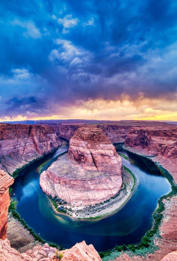 Courbure en fer à cheval sur le fleuve Colorado au coucher du soleil avec le ciel nuageux dramatique, Utah photographie stock