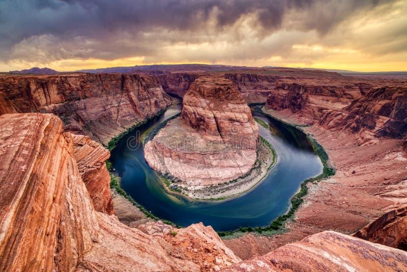 Courbure en fer ? cheval sur le fleuve Colorado au coucher du soleil avec le ciel nuageux dramatique, Utah images libres de droits