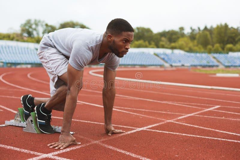 Coureur afro-américain convenable en position de départ sur le stade photographie stock