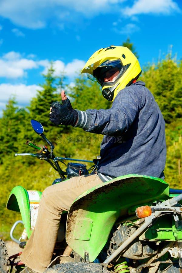 Coureur avec le casque jaune sur le quadruple vert appréciant le sien tour dehors, montrant le geste CORRECT photographie stock libre de droits