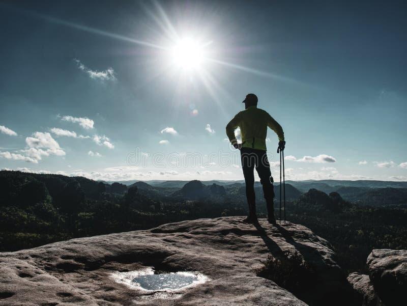 Coureur d'athlète d'homme avec des poteaux de trekking courant la traînée rocheuse images libres de droits