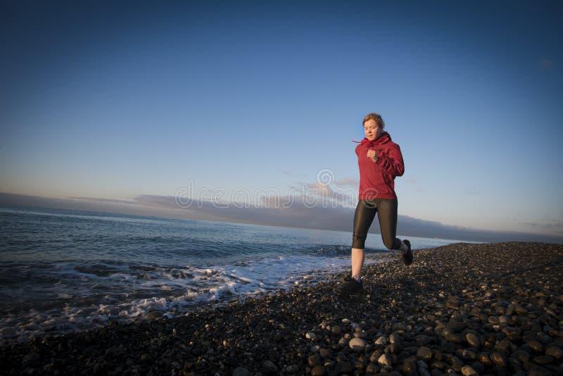 Coureur de femme adulte fonctionnant sur le bord de la mer de lever de soleil Style de vie sain photos libres de droits