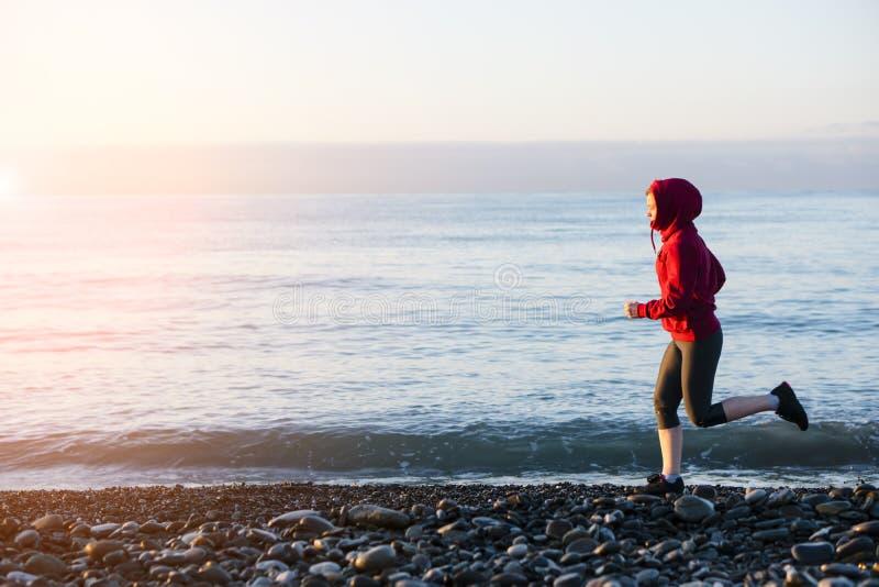 Coureur de femme adulte fonctionnant sur le bord de la mer de lever de soleil Style de vie sain photographie stock libre de droits