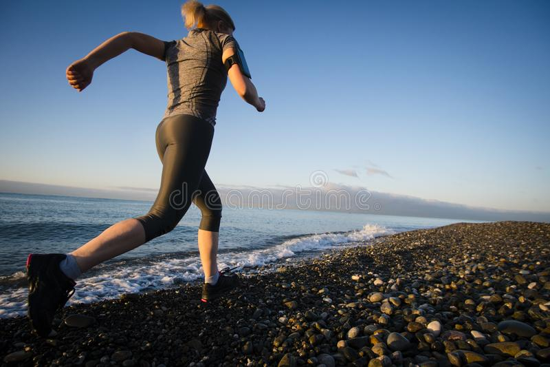 Coureur de femme adulte fonctionnant sur le bord de la mer de lever de soleil Style de vie sain image libre de droits