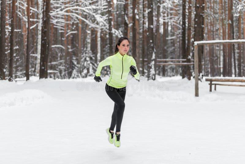 Coureur de femme d'athlète fonctionnant en parc ou forêt d'hiver photo stock