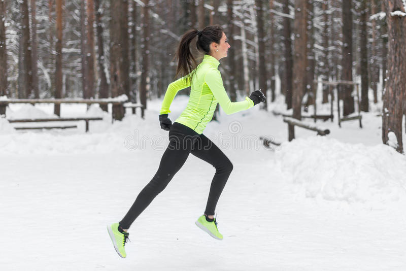 Coureur de femme d'athlète fonctionnant par temps de chute de neige froid Cardio- pulser de marathon de formation de rue photo stock