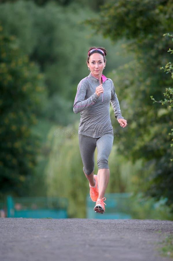 Coureur de femme de sports de forme physique fonctionnant sur la traînée de parc photo libre de droits