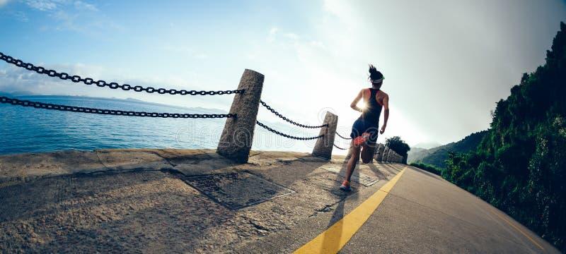 coureur de femme fonctionnant sur la route de bord de la mer de lever de soleil photo libre de droits