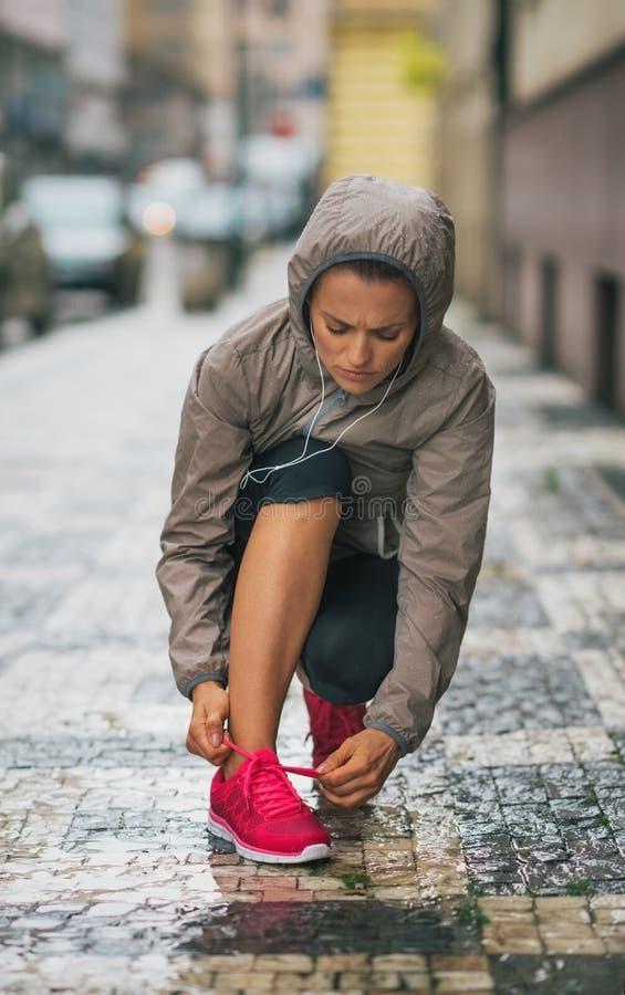Coureur de femme se mettant à genoux vers le bas pour attacher la chaussure de course sous la pluie photographie stock libre de droits