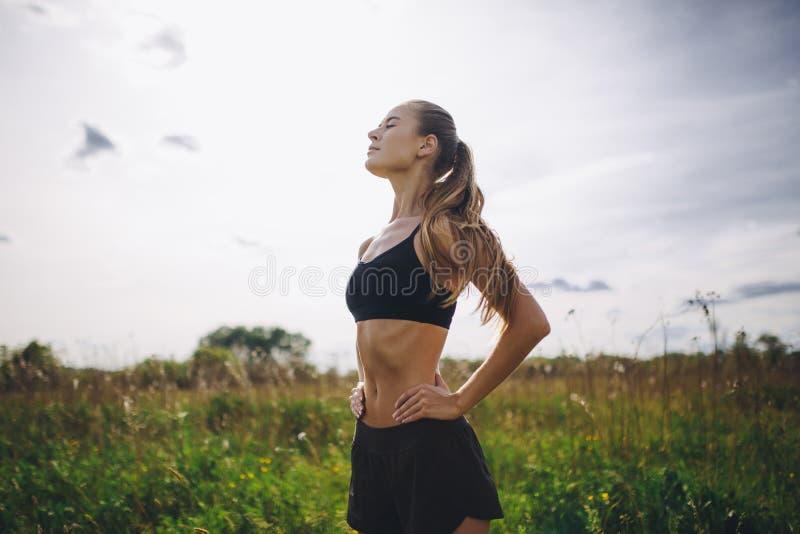Coureur de fille de sport de forme physique faisant la pause après avoir pulsé dehors photos stock