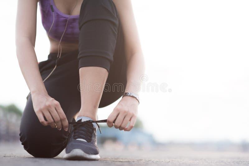 coureur de jeune femme attachant des dentelles avant la position pulsante sur les FO images libres de droits