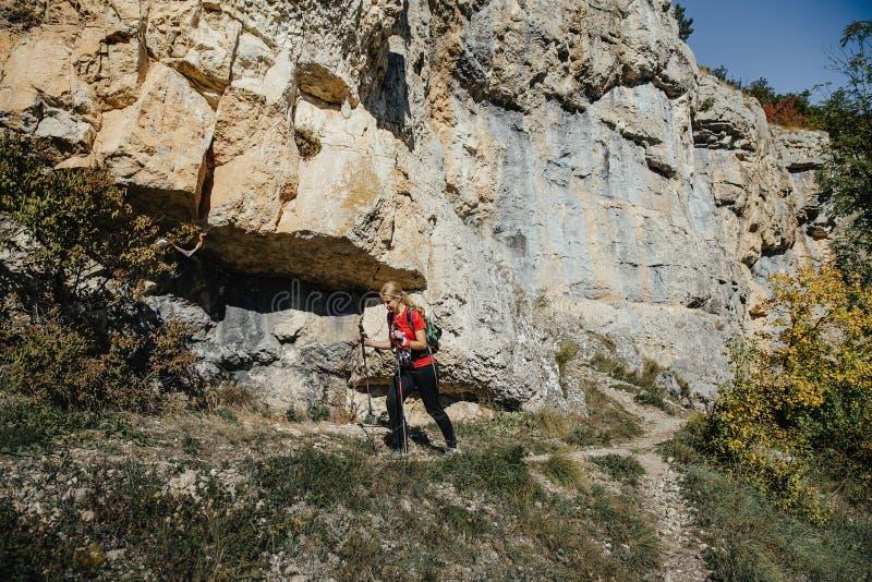 Coureur de jeune femme avec les poteaux de marche courant la traînée sur le fond des roches images libres de droits