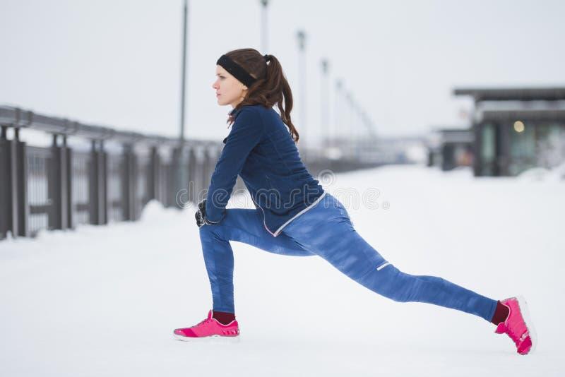 Coureur de jeune femme faisant l'exercice de flexibilité pour des jambes avant course à la promenade d'hiver de neige, image libre de droits
