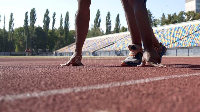 Coureur en position de départ sur la voie, formation de sportif avant la concurrence photographie stock libre de droits