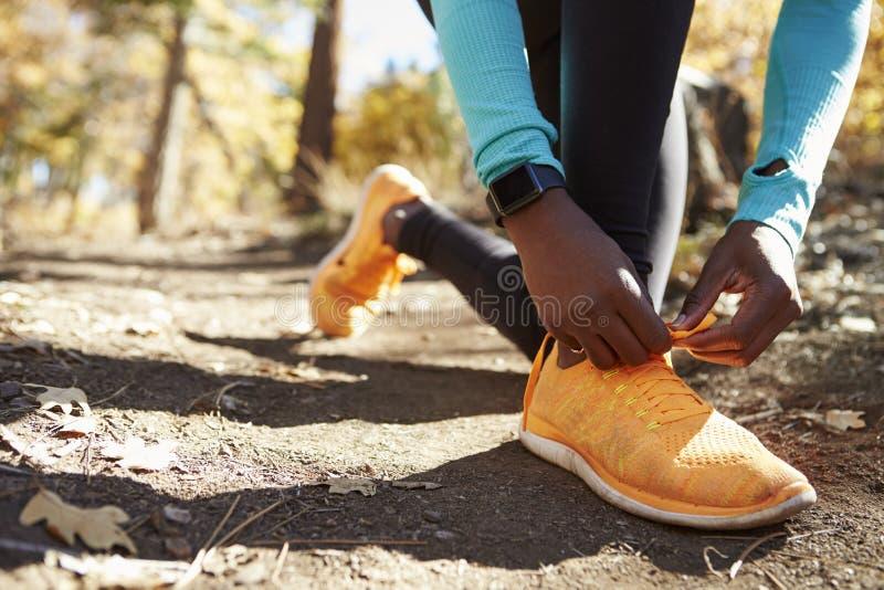 Coureur femelle noir dans la forêt attachant la chaussure, bas détail de section image libre de droits