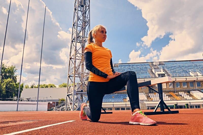 Coureur femelle sportif blond dans la position de début rapide images stock